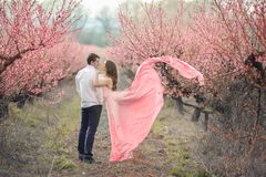 Romantic bridegroom kissing bride on forehead while standing against wall covered with pink flowers.  stock image