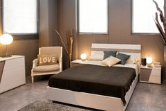 Romantic brown luxury bedroom interior. With divan style bed and chair with Love cushion illuminated by round lamps stock photos
