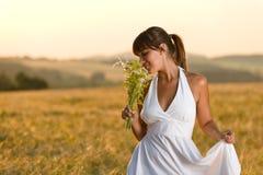 Romantic brunette woman in sunset corn field. Wear white dress, holding bouquet of flowers Royalty Free Stock Photos