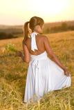 Romantic brunette woman in sunset corn field. Wear white dress, holding bouquet of flowers Stock Photo