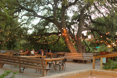 Romantic cafe in a park. Beautiful romantic cafe in park, with orange lights on trees Stock Image