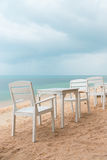 Romantic cafe with white tables and chairs on the sea shore royalty free stock images