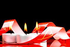 Romantic candles. Red ribbon and the burning candles Royalty Free Stock Images