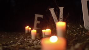 Romantic candles burning on road in a night park, white letters love on road in a night park, closeup stock video