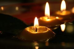 Romantic candles in the dark. These are candles in the dark. They create a romantic atmosphere. They float on the water in a glass container. The shape of the Stock Photo