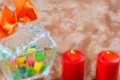 Romantic Candy. A romantic scene with a glass bowl full of candy with two lit red candles Stock Photography