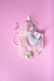 Romantic card or invitation. Heart, shells, veil, silk ribbon over pink background. Top view. Royalty Free Stock Images