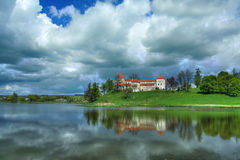 Romantic castle Svirzh 2. Svirzh castle above the lake and blue sky over it, Ukraine. HDR Stock Photography