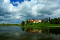 Romantic castle Svirzh. Svirzh castle above the lake and blue sky over it, Ukraine. HDR Stock Photo