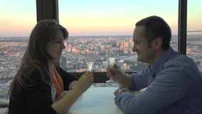 Romantic celebration on hotel terrace, lovers speaking and smiling, cheers with champagne, up city view, beautiful evening light. UHD 4K stock video footage