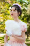 Romantic, charming girl fanning herself fan and with an attentive look. Romantic, charming girl in an evening dress in the image of the princess fanning herself royalty free stock photo