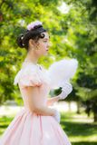 Romantic, charming girl fanning herself fan and with an attentive look. Romantic, charming girl in an evening dress in the image of the princess fanning herself stock image