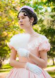 Romantic, charming girl fanning herself fan and with an attentive look. Romantic, charming girl in an evening dress in the image of the princess fanning herself stock photos