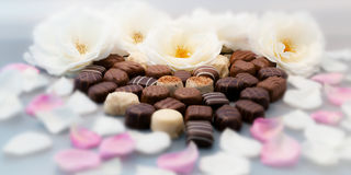 Romantic chocolate truffles and white roses heart shape setup horizontal Stock Photo