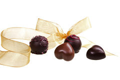 Romantic chocolate variation. Romantic luxurious chocolate heart variation with golden ribbon on white background stock images