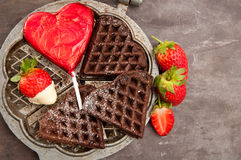 Romantic chocolate waffles. Home made heart shaped chocolate waffles served with strawberries and a heart shaped chocolate lollipop. A delicious, romantic Royalty Free Stock Photo