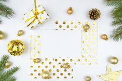 Romantic christmas composition. Paper blank, christmas tree branches, golden decorations and gift box on white. Christmas composition. Paper blank, christmas Stock Photo