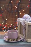 A wooden box with ornaments and a pink tea cup with a saucer. A romantic Christmas evening with a cup of hot fragrant tea in a pink cup with a saucer andd an Royalty Free Stock Image