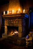 Romantic christmas interior. Fireplace room with chimney, candles and woodpile. Stock Photography