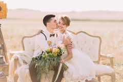 The romantic close-up portrait of the groom kissing the bride with the bouquet into the cheek in the sunny field. The Royalty Free Stock Images