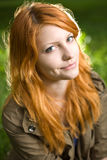 Romantic closeup portrait of a young redhead. Romantic closeup portrait of a young redhead girl sitting outdoors in the park stock photography