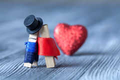 Romantic clothespin couple. Kissing. Man, woman. Gentleman in black hat and woman in red dress. Royalty Free Stock Images