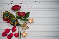 Romantic color christmas photography image with red roses lit candles and luxury chocolate with red and green bauble decorations. A photography image copy space stock images