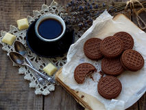 Romantic composition of chocolate cookies with white cream, cup of coffee and bouquet lavender on wooden background. Selective foc Stock Image