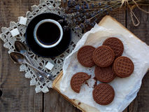 Romantic composition of chocolate cookies with white cream, cup of coffee and bouquet lavender on wooden background. Selective foc Royalty Free Stock Images