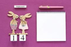 Romantic composition Cubes calendar February 14th Pair of wooden lovers figurine rabbits, open blank notebook for text with pen on stock photos