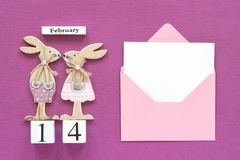 Romantic composition Cubes calendar February 14th Pair of wooden lovers figurine rabbits, pink envelope with blank card on purple stock photo