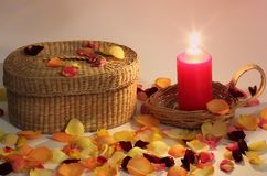 Romantic composition. Love. Wicker basket and braided candle and rose petals around royalty free stock image