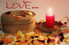 Romantic composition. Love. Wicker basket and braided candle and rose petals around stock photos