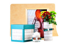 Romantic composition made of candle, flowers, songbook and box with a present. Stock Image