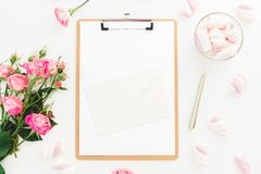 Romantic composition with marshmallow, pink roses, envelope and clipboard on white background. Top view. Flat lay. Romantic composition with marshmallow, pink Stock Photos