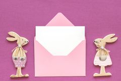 Romantic composition Pair of wooden lovers figurine rabbits and pink envelope with blank card on purple background Concept stock photo