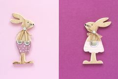 Romantic composition Pair of wooden lovers figurine rabbits on pink purple background Concept Valentine`s card Top view Flat Lay stock photos