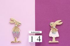 Romantic composition Wooden cubes calendar February 14th and pair of wooden lovers figurine rabbits on pink - purple background. Romantic composition Wooden stock photography
