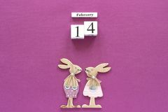 Romantic composition Wooden cubes calendar February 14th and pair of wooden lovers figurine rabbits on purple background. Concept. Valentine& x27;s card. Top royalty free stock images