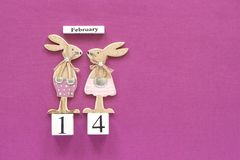 Romantic composition Wooden cubes calendar February 14th and pair of wooden lovers figurine rabbits on purple background. Concept. Valentine's card. Top stock photo