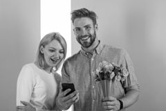 Romantic concept. Couple in love interested by phone. Man shows photo on smartphone to girl, sweet memories of their stock photos