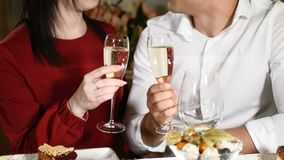 Romantic concept. happy couple eating dinner and drinking champagne, anniversary celebration. Woman and man, toast. Clinking with glasses in restaurant in the stock footage