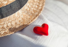 Romantic concept: straw hat and red heart Stock Photos