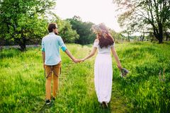 Young couple holding hands walking through a meadow royalty free stock photos