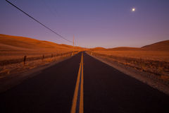 Romantic country road at dusk. Two lane country road at dusk in farm land country - idyllic dusk / dawn lighting Stock Photography