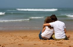 Romantic couple. Romantic young couple in casual clothes sitting on the sandy beach and looking to ocean Stock Photography