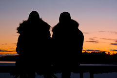 Romantic couple. The silhouettes of a couple siting down and watching the sunset Royalty Free Stock Images