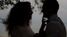 Romantic couple against the sky in the backlight. The young woman gently touches a finger on the nose of the beloved. Romantic couple against the sky in the stock video footage
