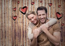 Romantic couple against wooden background. Portrait of romantic couple against wooden background with heart shapes Stock Photography