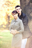Romantic couple in the autumn park. Attractive couple spending sunny day in the autumn park, golden leaves on  background Stock Image